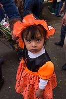 Mexico, Mexico City. Day of the Dead, Dia de los Muertos. Plaza Jamaica market. Girl dressed like pumpkin.