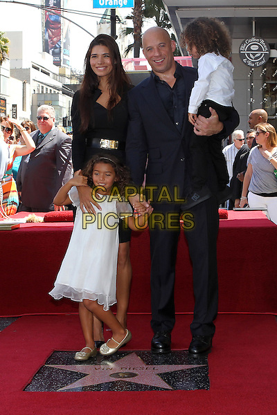 Paloma Jimenez, Hania Riley, Vin Diesel, Vin Diesel Jr.<br /> Vin Diesel honored with star on the Hollywood Walk Of Fame held on the Hollywood Walk Of Fame, Hollywood, California, USA.<br /> August 26th, 2013<br /> full length black suit white shirt carrying holding father dad son family kid child dress hands couple mother mom mum<br /> CAP/ADM/KB<br /> &copy;Kevan Brooks/AdMedia/Capital Pictures