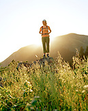 USA, California, Marin Headlands, young woman hiking and standing on a rock in front of Mount Tamalpais