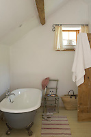 The attic bathroom is furnished with an old-fashioned roll top bath and is lit by a small square window