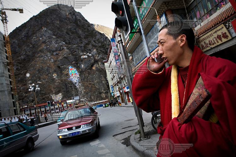 A monk talks on a mobile phone on the main street of Kanding.
