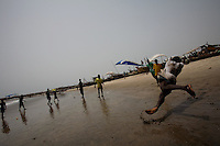 a boy plays soccer on the beach while awaiting for the 50th anniversary of his countries' independence in the Jamestown neighborhood in Accra, Ghana on Monday March 05 2007..