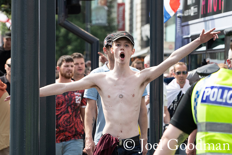 © Joel Goodman - 07973 332324 . 01/06/2018 . Leeds, UK. Supporters of EDL founder Tommy Robinson ( real name Stephen Yaxley-Lennon ) run through streets in Leeds City Centre and clash with police during a demonstration , after Robinson was convicted of Contempt of Court . Robinson was already serving a suspended sentence for Contempt of Court over a similar incident , when he was convicted on Friday 25th May 2018 . Reporting restrictions , since lifted , initially prevented coverage of Robinson's arrest and incarceration . Photo credit : Joel Goodman