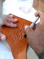 hands carving a design in leather.