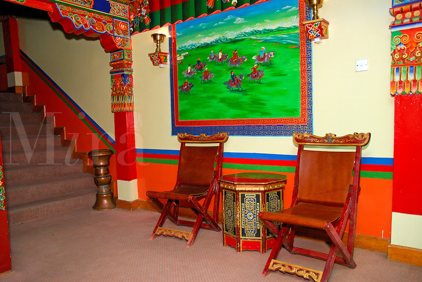 Mural, chairs and typical Tibetan painted hand-carved decor inside the Dhood Gu hotel, Lhasa, Tibet.