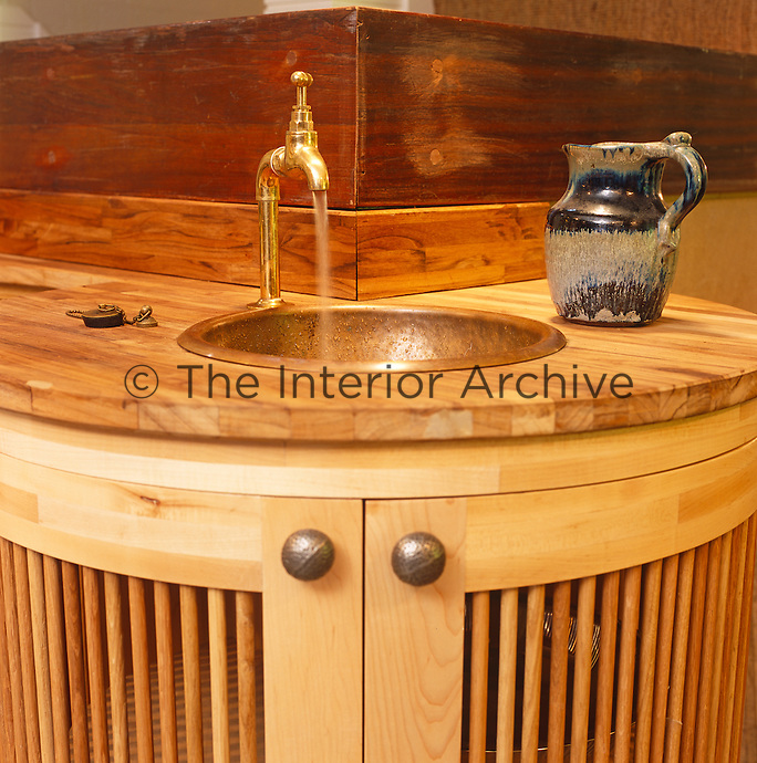 Close up of a copper basin mounted on a solid wood work surface