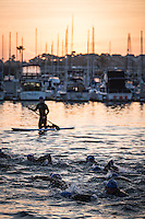 Age group athletes start the swim as the sun rises during the Accenture Ironman California 70.3 in Oceanside, CA on March 29, 2014.