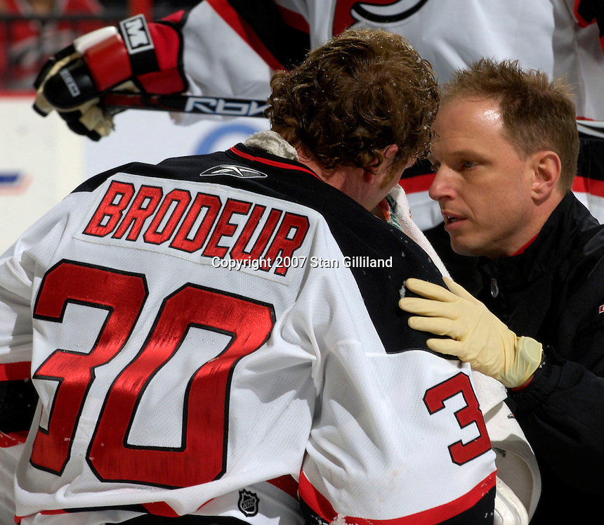 New Jersey Devils' goalie Martin Brodeur is attended by a team trainer after he took a stick to the nose during a game against the Carolina Hurricanes Thursday, March 15, 2007 at the RBC Center in Raleigh, NC. New Jersey won 3-2.