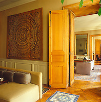 In the salon an exquisitely carved Mandala dominates an entire wall behind the contemporary velvet-covered sofa