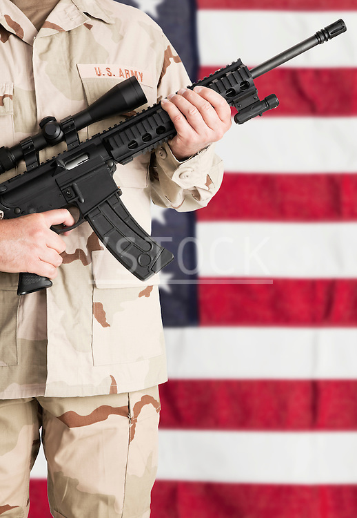 Studio shot of soldier with machine gun standing against American, mid section
