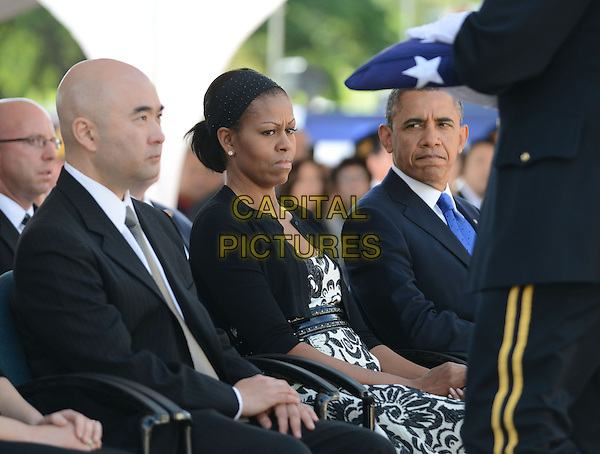 Michelle Obama look on as a flag is presented to Daniel Ken Inouye, Jr, son of the late U.S. Senator Daniel Inouye (Democrat of Hawaii) near the casket of the late Senator at the National Memorial Cemetery of the Pacific during funeral ceremonies on Sunday, December 23, 2012 . Senator Inouye was a Medal of Honor recipient and a U.S. Senator since 1963. .half length funeral first Lady sitting .CAP/ADM.©Cory Lum/CNP/AdMedia/Capital Pictures.