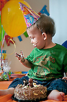 A young boy looks at his hand covered with cake during birthday party.