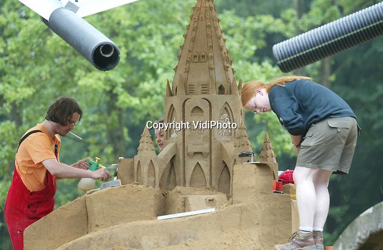 Foto: VidiPhoto..DIEREN - In de bossen van Dieren bouwen negen kunstenaars van het zandsnijderscollectief Zahara aan een Frans fantasie-stadje van zand, compleet met kasteel, kerken en een kerncentrale. Inspiratiebron is Mont St. Michel, een eilandje voor de Franse kust. Zaterdag moet het dorp klaar zijn. 's Avonds wordt het stadje sfeervol uitgelicht. Omdat het zandstadje grotendeels overdekt is, kunnen de sculpturen niet wegregenen.