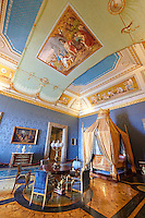 """The Bedroom of Francis II"". The room furnished with a four poster bed, chest of drawers and table in the Empire Style in mahogany & gilt. The vaulted ceiling is freaked with an allegory of the victory of Napoleon over the Bourbons: the Glory of Thesus slaying the Minataur, by Giuseppe Cammarano  .  The Bourbon Kings of Naples Royal Palace of Caserta, Italy."