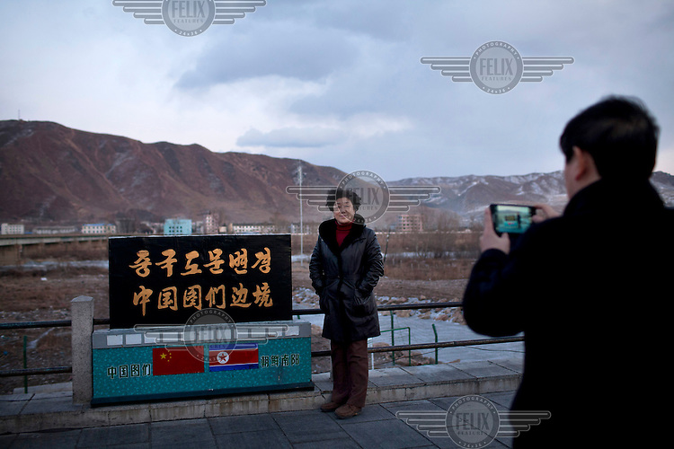 A Korean speaking tourist is photographed by her companion in front of a sign indicating the border with North Korea while in the background is the North Korean city of Nanyang. /Felix Features