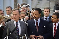 Washington DC., USA, December 1, 1988<br /> President -Elect George H.W. Bush stands with the Rev. Jesse Jackson in the driveway state-out area outside the entrance to the White House West Wing. To the Rev.'s left is his son Jesse Jackson Jr. who later represented Illinois's 2nd congressional detract in the U.S. House of Representatives. Bush is answering questions by members of the radio and televison reporters who routinely  stake out that area so as to catch VIP's as they come and go thru the official entrance to the appointments lobby of the White House. Credit: Mark Reinstein/MediaPunch