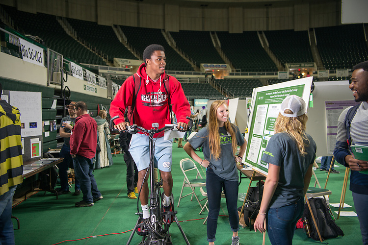 Studfent Jordan Patterson tries out an elliptical bike at Ohio University's Student Research and Creative Activity Expo. Photo by Ben Siegel
