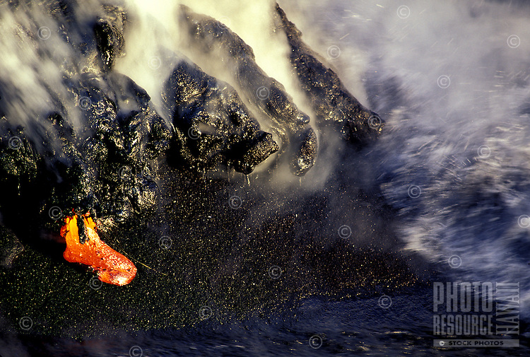 An orange/red tongue of molten lava juts out from hardened black lava rock on the Puna coast of Volcanoes National Park on the Big Island of Hawaii.
