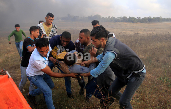 A wounded Palestinian protester is evacuated during clashes with Israeli security forces during tents protest demanding the right to return to their homeland, at the Israel-Gaza border, in Bureij in the cetner of Gaza strip on April 27, 2018. Photo by Mahmoud Khattab
