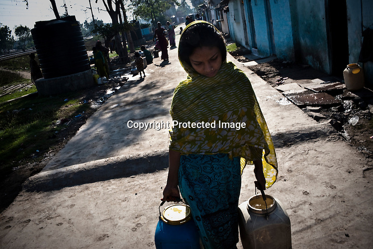 A young woman is seen carrying water from the broken pipes. The ground water is believed to be contaminated near the site of the deserted Union Carbide factory in Bhopal, India. Twenty-five years after an explosion causing a mass gas leak, in the Union Carbide factory in Bhopal, killed at least eight thousand people, toxic material from the 'biggest industrial disaster in history' continues to affect local Bhopalis. A new generation is growing up sick, disabled and struggling for justice. The effects of the disaster on the health of generations to come, both through genetics, transferred from gas victims to their children and through the ongoing severe contamination, caused by the Union Carbide factory, has only started to develop visible forms recently. Photograph: Sanjit Das