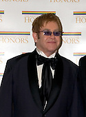 "2004 Kennedy Center Honoree Sir Elton John arrives at the Harry S. Truman Building (Department of State) in Washington, D.C. on December 4, 2004 for a dinner hosted by United States Secretary of State Colin Powell.  At the dinner six performing arts legends will receive the Kennedy Center Honors of 2004.  This is the 27th year that the honors have been bestowed on ""extraordinary individuals whose unique and abundant artistry has contributed significantly to the cultural life of our nation and the world"" said John F. Kennedy Center for the Performing Arts Chairman Stephen A. Schwarzman.  The award recipients are: actor, director, producer, and writer Warren Beatty; husband-and-wife actors, writers and producers Ossie Davis and Ruby Dee; singer and composer Elton John; soprano Joan Sutherland; and composer and conductor John Williams..Credit: Ron Sachs / CNP"