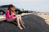 Charlott Crete (left), 9, and brother Andrew Crete, 6, eat snacks while sitting above their family on a recently-repaired portion of the parking lot embankment at Herring Cove Beach in the Cape Cod National Seashore outside of Provincetown, Mass., USA, on Fri., July 1, 2016. Portions of the parking lot have been closed after land eroded during storms earlier this year. The family is visiting Cape Cod from Saint-Sauveur, Quebec, Canada.