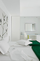 A guest bedroom continues the green and white decorative theme of the house