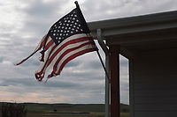 An American flag is tattered by the wind on a home near the pipeline route in ND on Monday, September 12, 2016. Many ranchers feel caught in the middle of the conflict between Enbridge and the protestors, who call themselves protectors. Some are reporting aggressive and threatening protestor behavior, like swearing, attempting to stop their vehicles, and carrying clubs.