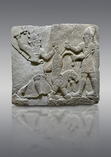 Hittite relief sculpted orthostat stone panel of Herald's Wall Basalt, Karkamıs, (Kargamıs), Carchemish (Karkemish), 900-700 B.C. Anatolian Civilisations Museum, Ankara, Turkey.<br /> <br /> On the right is a bearded human figure with a short skirt; with the dagger in his right hand, he is stabbing the lion standing on his front legs while holding the lion's tail with his left hand. On the left is a bearded god figure with a horned-headdress, who grasps the lion's hind leg while holding the ax over his head with his right hand.