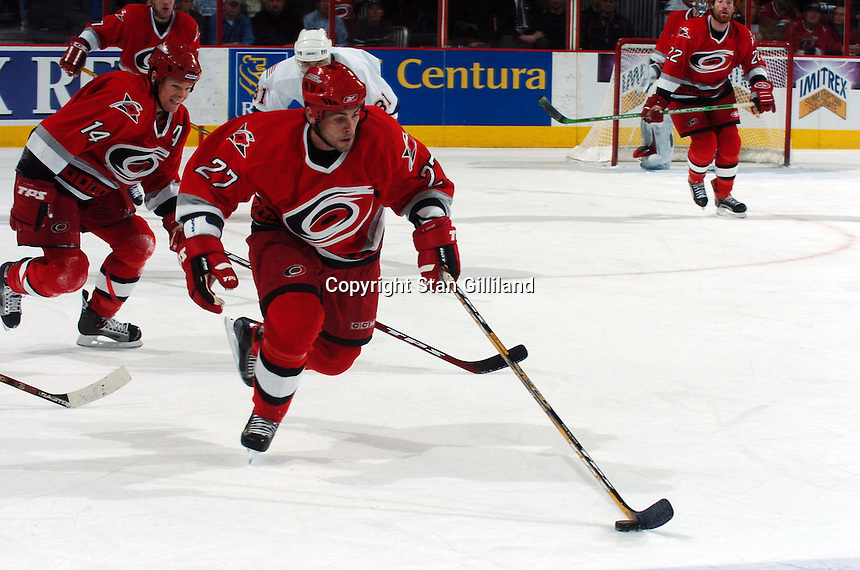 The Carolina Hurricanes' Craig Adams (27) pushes the puck up the ice trailed by teammate Kevyn Adams (14) during their game with the New York Islanders Thursday, Jan. 19, 2006 in Raleigh, NC. Carolina won 4-3.