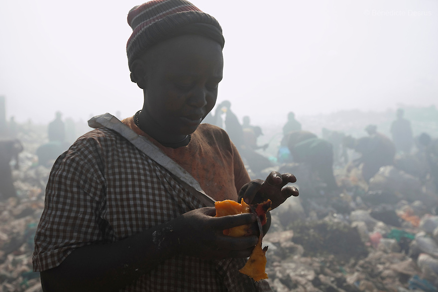 13 february 2013 - Dandora dumpsite, Nairobi, Kenya - A Kenyan woman eats a mango she found in the trash at the Dandora dumpsite, one of the largest and most toxic in Africa. Located near slums in the east of the Kenyan capital Nairobi, the open dump site was created in 1975 and covers 30 acres. The site receives 2,000 tonnes of unfiltered garbage daily, including hazardous chemical and hospital wastes. It is a source of survival for many people living in the surrounding slums, however it also harms children and adults' health in the area and pollutes the Kenyan capital. Photo credit: Benedicte Desrus