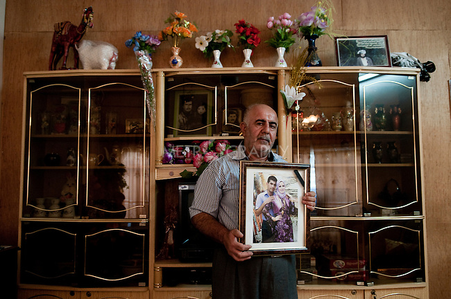 KIRKUK, IRAQ: Yasin Azadine holds a portrait of his son Sa'ad with his wife Saiwa. Both were killed in an explosion in Shorja on June 30, 2009...Kirkuk, the oil-rich city in northern Iraq, is home to Kurds, Arabs, Turkomen, Christians, Kakayi, and numerous other ethnicities. Since 2003, thousands of its residents have been killed or injured in terrorist attacks...As the US military leaves Iraq, the future of this violent and ethnically diverse city remains unsure...Photo by Pazhar Mohammad/Metrography