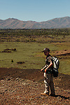 A young boy looks toward the camera with the landscape of Craters of the Moon National Monument in the background.