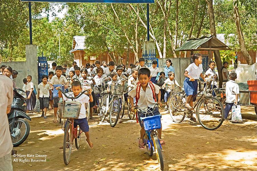 Cambodian boys and girls in uniforms leave school through gate on bikes and walk on dirt road in Siem Reap, Cambodia