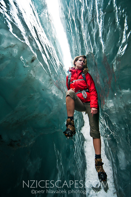 Beautiful woman walking through deep and  beautiful ice crevasse on Franz Josef Glacier - Westland National Park, West Coast, New Zealand