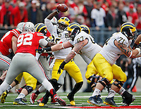 Michigan Wolverines quarterback Devin Gardner (98) slips away from an Ohio State Buckeyes sack in the 2nd quarter of their game at Ohio Stadium in Columbus, Ohio on November 29, 2014.  (Dispatch photo by Kyle Robertson)