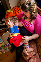 "A woman  7 months pregnant breastfeeds her little girl aged nearly 3 years old on the sofa in her living room. The little girl is waving at the camera.<br /> <br /> Image from the ""We Do It In Public"" documentary photography project collection: <br />  www.breastfeedinginpublic.co.uk<br /> <br /> Dorset, England, UK<br /> 14/02/2013"