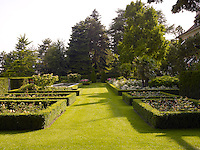 Framed beds of rose bushes and a rectangular pond are features of this well-stocked garden