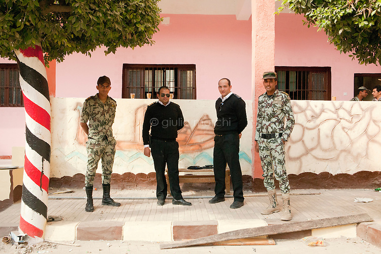 Egypt / Zagazig / 15.12.2012 / Police and army stand together posing for portrait in a polling station in Zagazig. People descended on polling stations across Egypt to vote on the highly controversial draft constitution, which has been a source of intense political protest in recent weeks. <br /> <br /> © Giulia Marchi