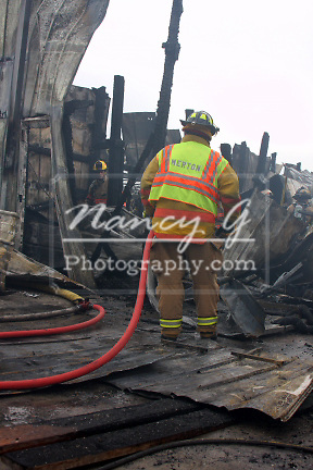 Merton Firefighter holding a hoseline for firefighters searching for hot spots in a collapsed building
