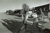 UPINGTON, SOUTH AFRICA - FEBRUARY 8: A man and a woman fight along a street February 8, 2002 in Loisevale near Upington, South Africa. Loisevale is a poor and destitute black township where unemployment is high and a number of social problems exist including domestic violence and alcohol abuse. Baby Thsepang, an eight-month old baby, was raped by her father in a house on this street in October 2001. The baby rape shocked the country. South Africa is struggling with an increasing number of rapes and sexual abuse of young children. In addition, the country has the highest number of rapes in the world. (Photo by Per-Anders Pettersson)