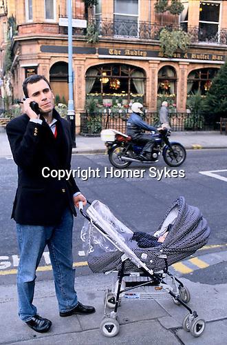 Man pushing child in pram, Mayfair London 1980s.