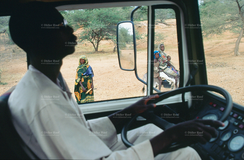 Sudan. West Darfur. Habilah. The non-governmental organization (ngo) Médecins sans Frontières (MSF) Switzerland runs a medical program. The MSF truck driver is carefully holding his streering wheel  while overpassing a mother and her two children riding a donkey. © 2004 Didier Ruef
