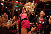 Kategory 5, in the jean jacket, talks with Glitterotica, to her right, and Hot T'Wally at Barton Springs Saloon after a bout between the Hellcats and Putas del Fuego in Austin, Texas.