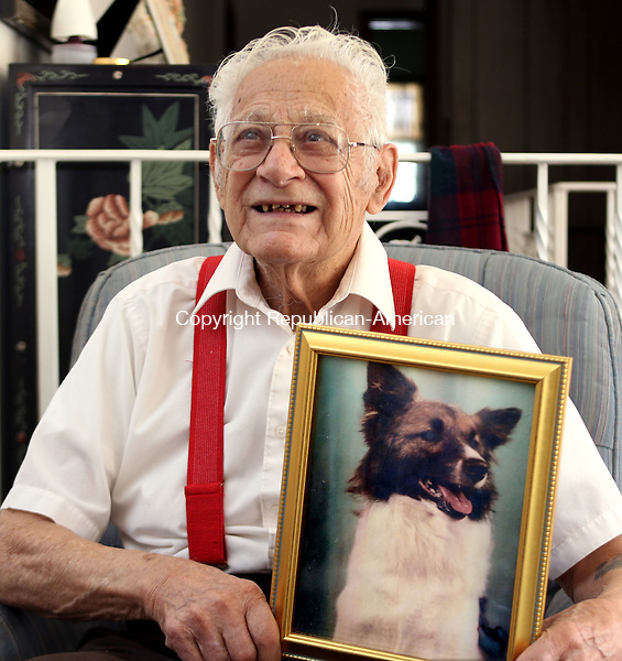 WATERBURY CT. 08 November 2016-110816SV01-Frank Barbino sits with a portrait of his dog from years ago at his home in Waterbury Thursday. Barbino served at Pearl Harbor at the end of WWII (non combat). There, he adopted a dog that he shipped home. Together, they rode all over Waterbury on a motorcycle. Recently, they were reunited when a portrait of the dog was found at a relative's house. <br /> Steven Valenti Republican-American