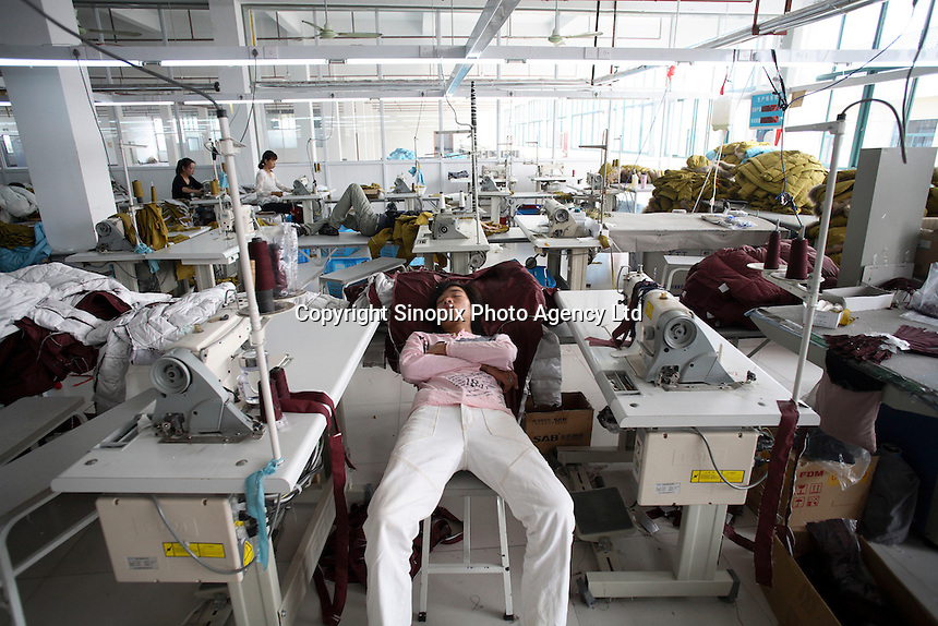 A worker takes a nap during lunch break at the Quanli Garment Factory in Pinghu, Zhejiang Province, China. It is a normal practice for factory workers to sleep during lunch breaks in China. The textile industry in China suffers severe difficulties since 2008. .