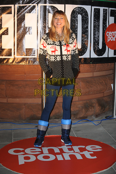 Sara Cox .The Centrepoint 'Sleep Out' event at Exchange Square, London, England..10th November 2011 .full length black white red sweater hands in pockets jeans denim boots jumper festive reindeer poppy top snowflakes .CAP/WIZ.© Wizard/Capital Pictures.