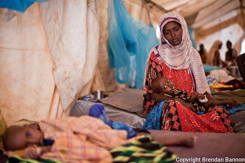 "Fatuma Badel fled Buale, Somalia with 8 children after leaving her sick husband. ""He became sick and I couldn't carry him. I don't know if he is alive or dead. This one, my youngest child was like a dead person when I arrived. Now I thank God I can hear him cry again.""  Badel has spent 3 days in the Doctors Without Borders hospital with her baby Mohamud who arrived severely malnourished. At nine months old he weighs 4.3 KG. Dadaab refugee camp, Kenya July 22, 2011. Photo: Brendan Bannon"