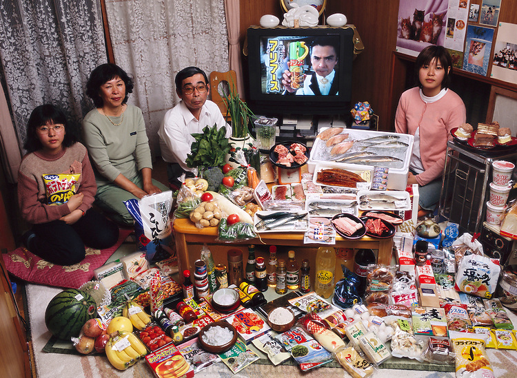 (MODEL RELEASED IMAGE). The Ukita family: Sayo Ukita, 51, and her husband, Kazuo Ukita, 53, with children Maya, 14 (holding chips) and Mio, 17 in their dining room in Kodaira City, Japan, with one week's worth of food. The Ukita family is one of the thirty families featured in the book Hungry Planet: What the World Eats (p. 180).