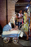 Senigallia, Agosto 2013. Due ragazzi con un passeggino vestiti stile anni 60 nei vicoli di Senigallia durante il Festival Summer Jamboree.